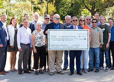 CSUF Campus Community Members gather around giant check.