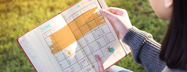Woman holding a small planner with notes and highlighted dates