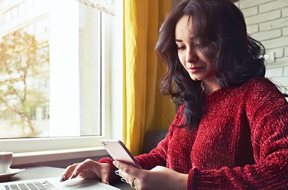 Woman using a laptop and a smartphone