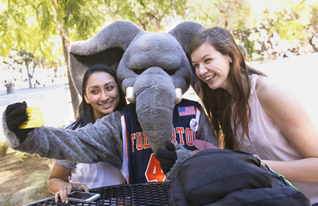two students and Cal State Fullerton mascot Tuffy