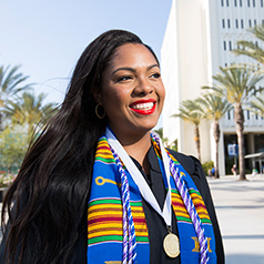 Young woman waving during the 2016 CSUF commencement ceremony