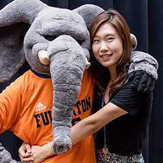 International student embracing CSUF mascot Tuffy the elephant