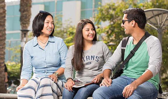 Three international students smiling and talking while sitting outside on campus