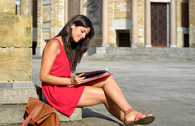 Female student sitting and studying on the steps of a historic building abroad