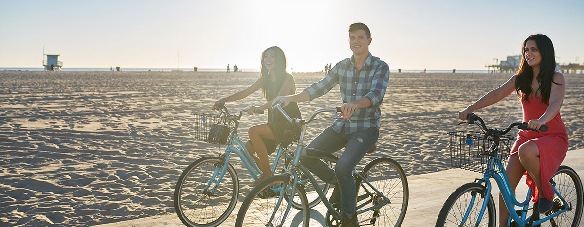 Group of students riding bikes at the beach